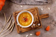 Puré de la sopa de la calabaza en un cuenco de cerámica con el condimento picante de la pimienta de chile en la atmósfera todavía imagen de archivo libre de regalías