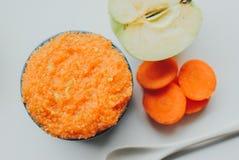 Puré de la zanahoria de los alimentos para niños con las manzanas verdes en cuenco de cerámica Fotos de archivo