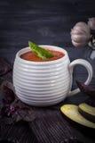Puré hecho en casa de la sopa con la berenjena, los tomates, el calabacín y el ajo en un fondo de madera oscuro Imágenes de archivo libres de regalías