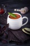 Puré vegetariano hecho en casa de la sopa con la berenjena, los tomates, el calabacín y el ajo en un fondo de madera oscuro Fotografía de archivo