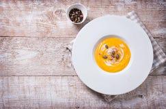 Purée crémeuse savoureuse faite maison de soupe à potiron dans une cuvette sur un fond en bois Photos libres de droits