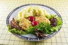 Purée de pommes de terre avec les côtelettes, le radis, l'oignon et la salade de poulet sur la table du ` s de cuisine photographie stock libre de droits