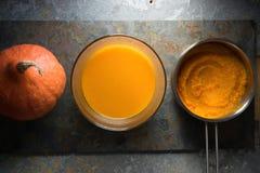 Purée de potiron dans une casserole, une soupe à potiron et un potiron sur une pierre grise Photo libre de droits