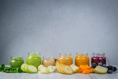 Purés coloridos do comida para bebê nos frascos de vidro Imagem de Stock Royalty Free
