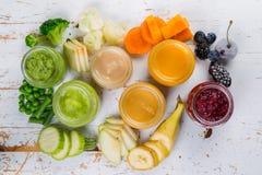 Purés coloridos do comida para bebê nos frascos de vidro Fotografia de Stock Royalty Free