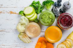 Purés coloridos do comida para bebê nos frascos de vidro Fotos de Stock Royalty Free