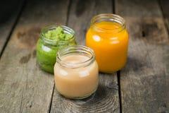 Purés coloridos do comida para bebê nos frascos de vidro Fotos de Stock
