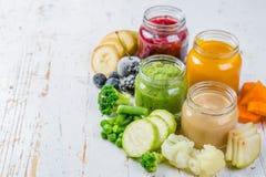 Purés coloridos do comida para bebê nos frascos de vidro Imagens de Stock Royalty Free