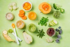 Purés coloridos do comida para bebê nos frascos de vidro Imagens de Stock