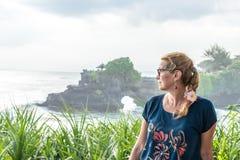 Pura Tanah全部寺庙,巴厘岛,印度尼西亚背景的妇女  免版税库存照片
