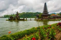 Pura Ulun Danu Batur temple in lake with flowers. Bali, Indonesia. Stock Images