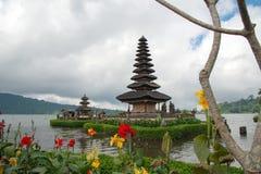 Pura Ulun Danu-Tempel auf einem See Beratan am bewölkten Tag mit grünem Gras und buntem Blumenvordergrund bei Bali, Indonesien lizenzfreie stockfotografie
