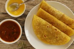 Puran Poli is a sweet flatbread made during special occasions or festival season. This bread is stuffed with sweet lentil stuffing and served with dollop of Stock Image