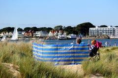 Purbeck Dorset, UK - Juni 02 2018: Man och och sittande koppla av för kvinnapar bak en traditionell brittisk vindskydd på sanddyn royaltyfria bilder
