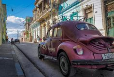A purble oldtimer beetle in the streets of santiago de cuba. A purble oldtimer beetle in a street lined with colorful old houses in santiago de cuba Royalty Free Stock Image