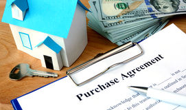 Purchase agreement document with home model. Royalty Free Stock Photos