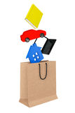 Purchase concept. Book, laptop, car and house drop in paper bag Stock Photo