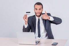 Purchase by credit card. Successful African businessman sitting Stock Image