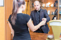 Purchase a jewelry store. Jewelry store owner is passing a sold product to his buyer, a young woman stock photo
