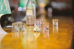 Purchase and payment. Cash money concept. Leave tips for bartender. Tip given to waiter. Crumpled money cash at bar. Counter. Empty glasses and bottle on table royalty free stock images