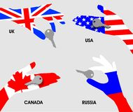 Purchase of real estate or other private property in Russia, USA, UK, Canada. Hands national flags holding the keys on a gray. Royalty Free Stock Images
