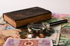 Purchase, sale and pledge antiques. Old antigue vintage book, collection of paper money banknote bills, ancient coins and retro magnifying glass, close-up Royalty Free Stock Photography