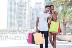 This purchase is for you. Couple hugging and holding shopping ba Stock Photography