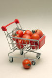 Purchases. Little shopping trolley with tomatoes Stock Photo