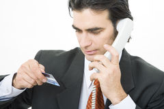 Purchasing. Businessman purchasing something over the phone with a credit card Royalty Free Stock Photography