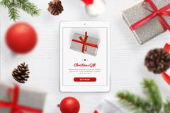 Purchasing Christmas gifts online. Tablet on the table, surrounded by Christmas gifts stock photos
