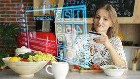 Purchasing Online Through Hologram Interface Panel. Woman uses futuristic hologram panel for online purchasing, entering credit card numbers through innovational stock video footage