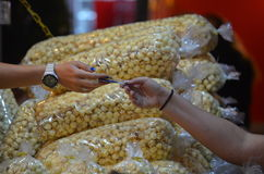 Purchasing Popcorn. Giving a credit card to a merchant to buy popcorn. Hands are exchanging the card. Popcorn bags in the background royalty free stock photo