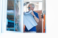 Thoughtful grey haired man choosing a T-shirt royalty free stock images