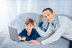Happy father patting head of his son chatting online. Pure affection. Upbeat pleasant men lying on the bed next to his son and patting his head fondly while the Royalty Free Stock Photography