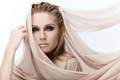 Pure beauty. Portrait of a young beautiful lady covered with beige fabrics Stock Image