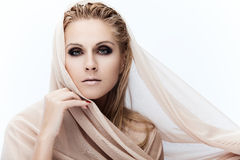 Pure beauty. Portrait of a young beautiful lady covered with beige fabrics Royalty Free Stock Photos