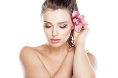 Pure Beauty. Young beautiful woman posing with orchid royalty free stock image
