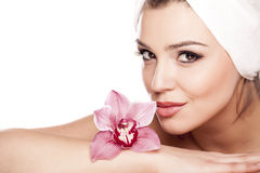 Pure Beauty. Young beautiful woman with a towel on her head enjoying the scent of orchids Stock Photo