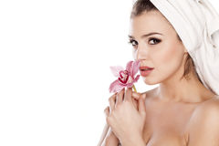 Pure Beauty. Young beautiful woman with a towel on her head enjoying the scent of orchids stock image