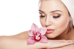 Pure Beauty. Young beautiful woman with a towel on her head enjoying the scent of orchids Royalty Free Stock Photo