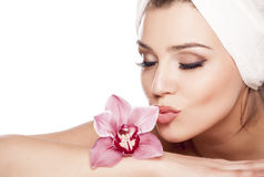 Pure Beauty. Young beautiful woman with a towel on her head and kissing orchid Royalty Free Stock Image