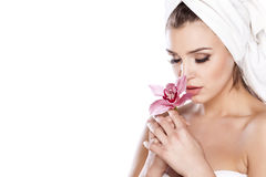 Pure Beauty. Young beautiful woman with a towel on her head posing with orchid Royalty Free Stock Photos