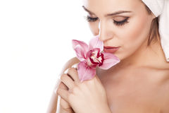 Pure Beauty. Young beautiful woman with a towel on her head posing with orchid royalty free stock images
