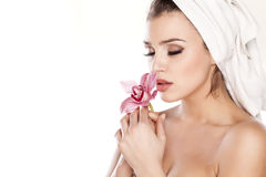Pure Beauty. Young beautiful woman with a towel on her head posing with orchid Royalty Free Stock Photo