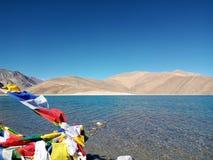 Pure Blue Pangong tso (Lake) and colorful religious flags Stock Photos