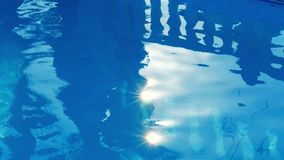 Pure blue water in the pool with light reflections of a girl silhouette in sunny day. Cyprus. stock footage
