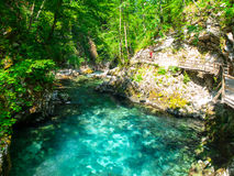 Pure blue water of Radovna river in Vintgar Gorge. Natural waterfalls, pools and rapids and tourist wooden path Royalty Free Stock Photo