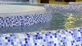 Pure blue water in swimming pool. Is moving in circle. Motion of fluid under pressure in given direction. SPA-relaxing in warm bubble bath. Stylish interior stock footage