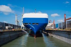 Pure car carrier on dock. Roll-on roll-off vessel white color on top and blue color down below on dock for repair view from stern can see rudder and propeller royalty free stock image
