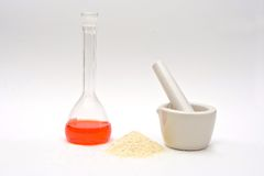 Pure chemistry. A red liquid in a flask with a powder in front and a white mortar isolated on a white background royalty free stock image